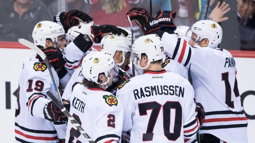 Chicago Blackhawks' Marian Hossa, center left, of Slovakia, and his teammates celebrate his winning goal against the Vancouver Canucks during the overtime period of an NHL hockey game in Vancouver, British Columbia, on Saturday Nov. 19, 2016. (Darryl Dyck/The Canadian Press via AP)
