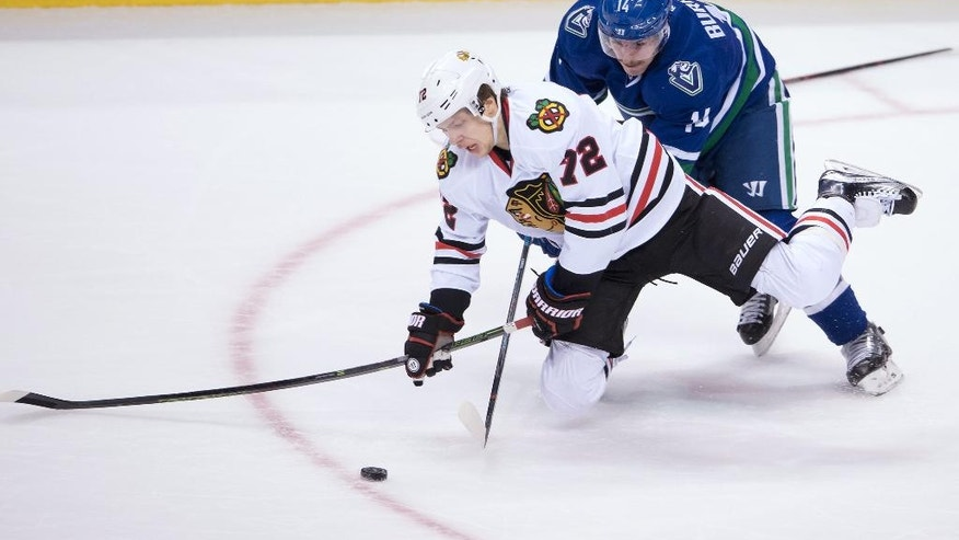 Vancouver Canucks' Alex Burrows, back, checks Chicago Blackhawks' Artemi Panarin, of Russia, during the third period of an NHL hockey game in Vancouver, British Columbia, on Saturday Nov. 19, 2016. (Darryl Dyck/The Canadian Press via AP)