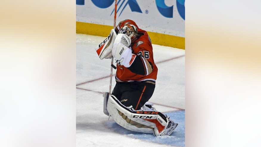 Anaheim Ducks goalie John Gibson covers up after blocking a puck high off the Los Angeles Kings in the second period of an NHL hockey game in Anaheim, Calif., Sunday, Nov. 20, 2016. (AP Photo/Reed Saxon)