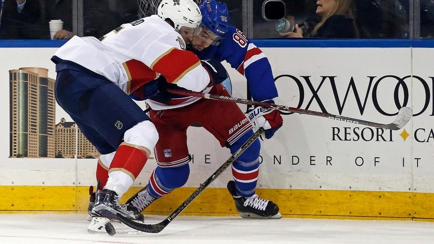 Florida Panthers defenseman Aaron Ekblad (5) and New York Rangers center Josh Jooris (86) battle for control of the puck in the second period of an NHL hockey game Sunday, Nov. 20, 2016, in New York. (AP Photo/Adam Hunger)