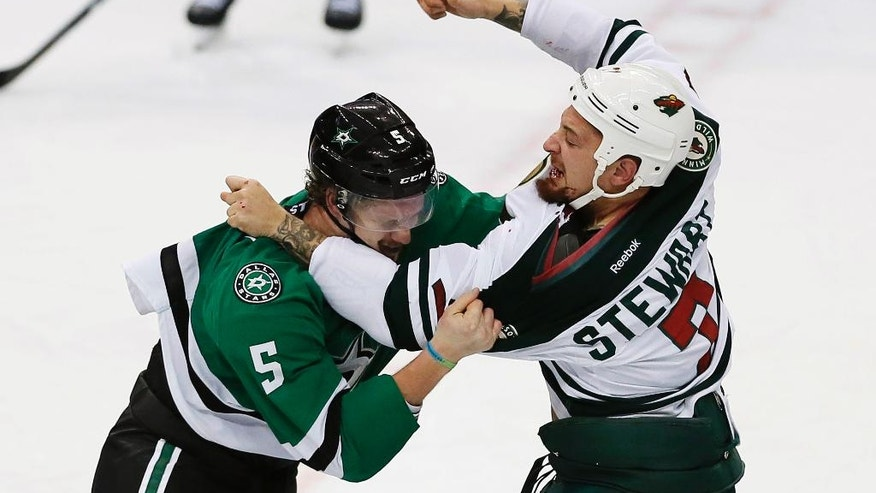 Dallas Stars defenseman Jamie Oleksiak (5) and Minnesota Wild forward Chris Stewart (7) fight during the first period of an NHL hockey game Monday, Nov 21, 2016, in Dallas. (AP Photo/Brandon Wade)