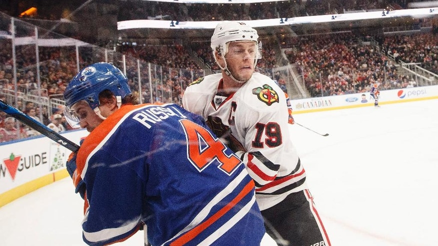 Chicago Blackhawks' Jonathan Toews (19) and Edmonton Oilers' Kris Russell (4) battle for the puck during first period NHL hockey action in Edmonton, Alberta, Monday Nov. 21, 2016. (Jason Franson/The Canadian Press via AP)
