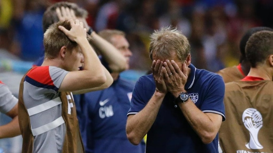"FILE - In this July 1, 2014, file photo, United States' head coach Juergen Klinsmann reacts during the World Cup round of 16 soccer match between Belgium and the USA at the Arena Fonte Nova in Salvador, Brazil. Klinsmann is out as coach of the U.S. soccer team. U.S. Soccer Federation President Sunil Gulati announced Monday, Nov. 21, 2016, that Klinsmann has been ""relieved of his duties"" as coach and technical director for U.S. Soccer.  (AP Photo/Matt Dunham, File)"