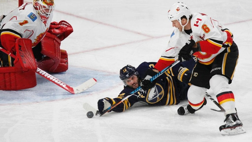 Buffalo Sabres forward Brian Gionta (12) is tripped up by Calgary Flames defenseman Dennis Wideman (6) during the second period of an NHL hockey game, Monday, Nov. 21, 2016, in Buffalo, N.Y. (AP Photo/Jeffrey T. Barnes)