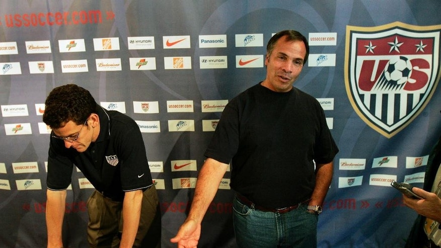 FILE - In this June 23, 2006, file photo, United States team manager Bruce Arena, right, speaks to journalists about being eliminated from the 2006 soccer World Cup at a news conference in Hamburg, Germany, as press officer Michael Kammarman listens at left. Arena is returning to coach the U.S. national team, a decade after he was fired.  The winningest coach in American national team history, Arena took over Tuesday, Nov. 22, 2016, one day after Jurgen Klinsmann was fired.  (AP Photo/Elise Amendola, File)