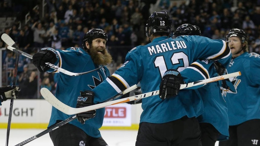 San Jose Sharks' Joe Thornton, left, congratulates Patrick Marleau (12) after Marleau scored against the New Jersey Devils during the first period of an NHL hockey game Monday, Nov. 21, 2016, in San Jose, Calif. (AP Photo/Ben Margot)