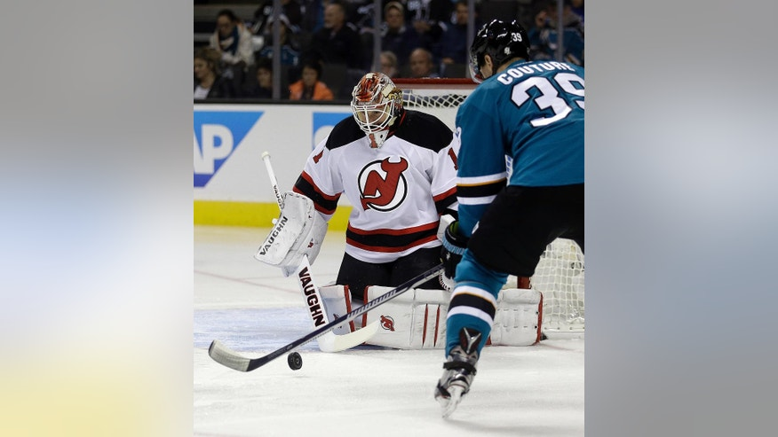 San Jose Sharks' Logan Couture, right, shoots against New Jersey Devils goalie Keith Kinkaid (1) during the first period of an NHL hockey game Monday, Nov. 21, 2016, in San Jose, Calif. (AP Photo/Ben Margot)