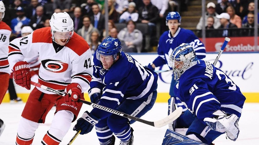 Toronto Maple Leafs goalie Frederik Andersen (31) makes a save against Carolina Hurricanes' Joakim Nordstrom (42) as Maple Leafs' Morgan Rielly (44) defends during the first period of an NHL hockey game in Toronto on Tuesday, Nov. 22, 2016. (Frank Gunn/The Canadian Press via AP)