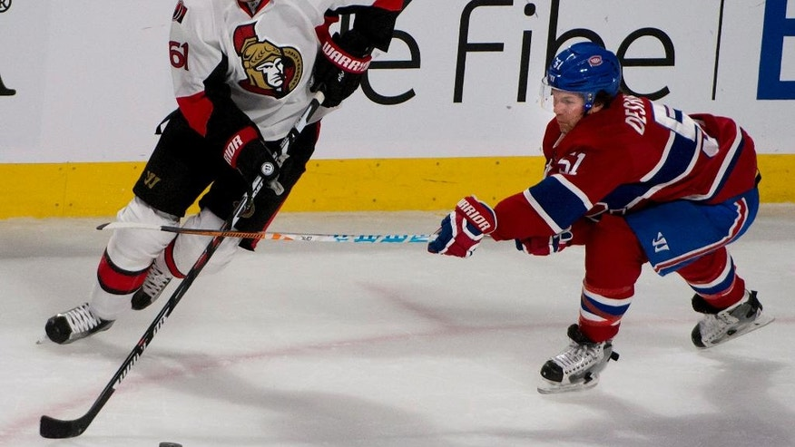 Montreal Canadiens' David Desharnais, right, checks Ottawa Senators' Mark Stone during the first period of an NHL hockey game, Tuesday, Nov. 22, 2016 in Montreal. (Peter McCabe /The Canadian Press via AP)