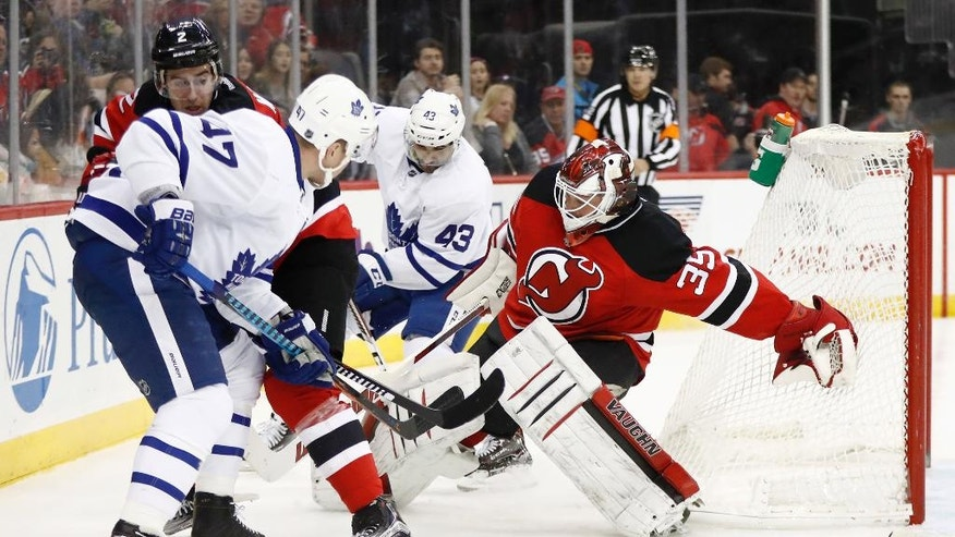 New Jersey Devils goalie Cory Schneider, right, tries to keep his balance while defending against the Toronto Maple Leafs during the first period of an NHL hockey game, Wednesday, Nov. 23, 2016, in Newark, N.J. (AP Photo/Julio Cortez)