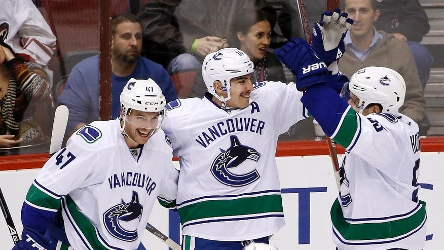 Vancouver Canucks right wing Alexandre Burrows (14) celebrates his goal against the Arizona Coyotes with left wing Sven Baertschi (47) and center Bo Horvat, right, during the second period of an NHL hockey game Wednesday, Nov. 23, 2016, in Glendale, Ariz. (AP Photo/Ross D. Franklin)
