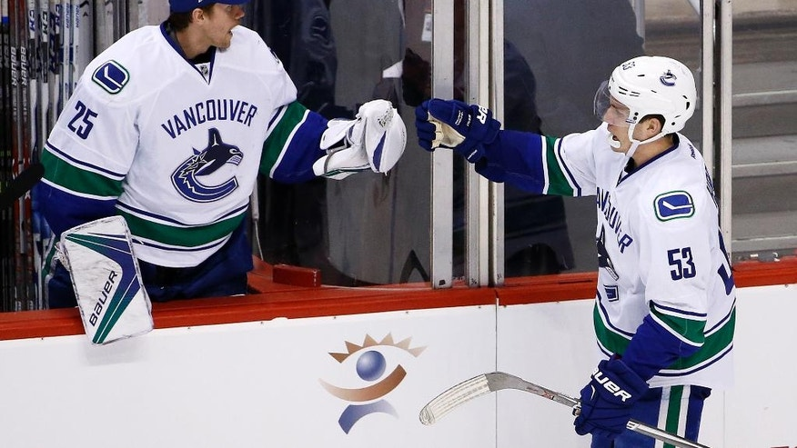 Vancouver Canucks center Bo Horvat (53) celebrates his goal against the Arizona Coyotes with Canucks goalie Jacob Markstrom (25) during the second period of an NHL hockey game Wednesday, Nov. 23, 2016, in Glendale, Ariz. (AP Photo/Ross D. Franklin)