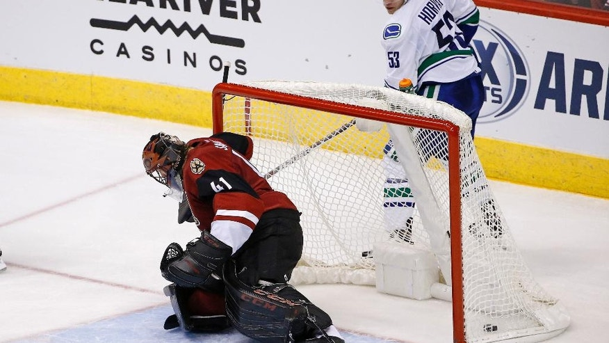 Arizona Coyotes goalie Mike Smith (41) gives up a goal to Vancouver Canucks right wing Alexandre Burrows as Canucks center Bo Horvat (53) watches during the second period of an NHL hockey game Wednesday, Nov. 23, 2016, in Glendale, Ariz. (AP Photo/Ross D. Franklin)
