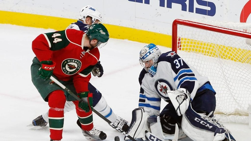 Minnesota Wild's Tyler Graovac, left, tries to work a rebound past Winnipeg Jets goalie Connor Hellebuyck during the second period of an NHL hockey game Wednesday, Nov. 23, 2016, in St. Paul, Minn. (AP Photo/Jim Mone)