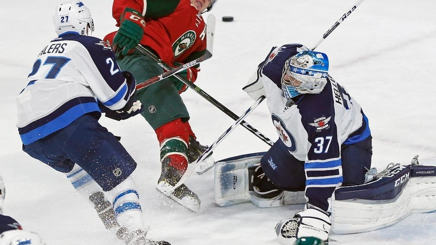 Minnesota Wild's Zach Parise, center, gets a shove from Winnipeg Jets' Nikolaj Ehlers, left, of Denmark as Jets goalie Connor Hellebuyck, right, watches during the first period of an NHL hockey game Wednesday, Nov. 23, 2016, in St. Paul, Minn. (AP Photo/Jim Mone)