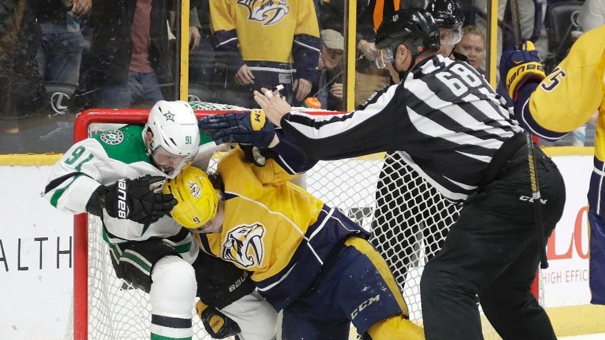 Dallas Stars center Tyler Seguin (91) and Nashville Predators left wing Filip Forsberg (9), of Sweden, fight inside the net as linesman Scott Driscoll (68) tries to break it up during the second period of an NHL hockey game Wednesday, Nov. 23, 2016, in Nashville, Tenn. (AP Photo/Mark Humphrey)