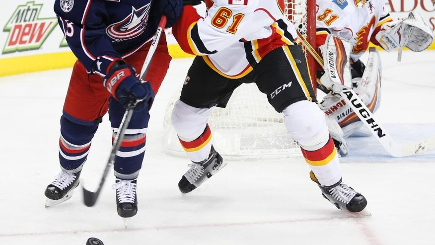 Columbus Blue Jackets' Cam Atkinson, left, and Calgary Flames' Brett Kulak fight for a loose puck during the second period of an NHL hockey game Wednesday, Nov. 23, 2016, in Columbus, Ohio. (AP Photo/Jay LaPrete)