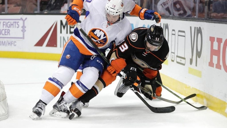 New York Islanders' Alan Quine, left, and Anaheim Ducks' Shea Theodore fight for the puck during the first period of an NHL hockey game, Tuesday, Nov. 22, 2016, in Anaheim, Calif. (AP Photo/Jae C. Hong)