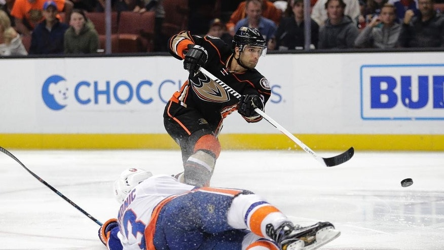Anaheim Ducks' Andrew Cogliano, top, shoots under pressure by New York Islanders' Travis Hamonic during the second period of an NHL hockey game, Tuesday, Nov. 22, 2016, in Anaheim, Calif. (AP Photo/Jae C. Hong)