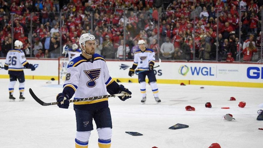 St. Louis Blues defenseman Kevin Shattenkirk (22) waits as hats litter the ice after Washington Capitals left wing Alex Ovechkin scored his third goal of the night for a hat trick during the third period of an NHL hockey game, Wednesday, Nov. 23, 2016, in Washington. The Capitals won 4-3. (AP Photo/Nick Wass)