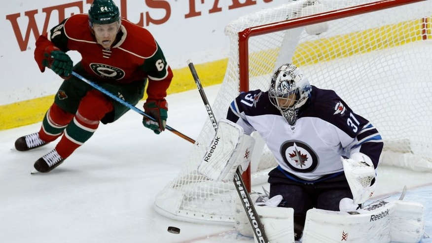 Winnipeg Jets goalie Ondrej Pavelec (31), of the Czech Republic, deflects a shot as Minnesota Wild center Mikael Granlund (64), of Finland, chases the rebound during the first period of an NHL hockey game in St. Paul, Minn., Saturday, Sept. 27, 2014. (AP Photo/Ann Heisenfelt)