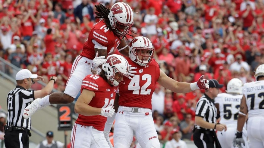 <p>Wisconsin's T.J. Watt, Leo Musso and D'Cota Dixon celebrate a safety during the first half against Akron.</p>