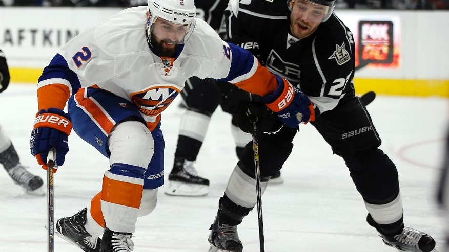 New York Islanders defenseman Nick Leddy, left, and Los Angeles Kings defenseman Alec Martinez, right, vie for the puck during the first period of an NHL hockey game in Los Angeles, Wednesday, Nov. 23, 2016. (AP Photo/Alex Gallardo)