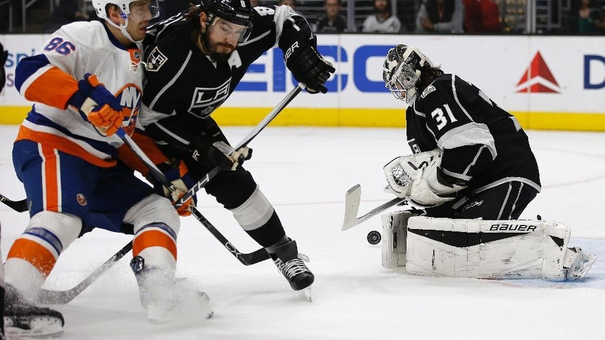 Los Angeles Kings goalie Peter Budaj, right, of Slovakia, stops the puck as defenseman Drew Doughty, center, holds back New York Islanders left wing Nikolay Kulemin, left, of Russia, during the first period of an NHL hockey game in Los Angeles, Wednesday, Nov. 23, 2016. (AP Photo/Alex Gallardo)