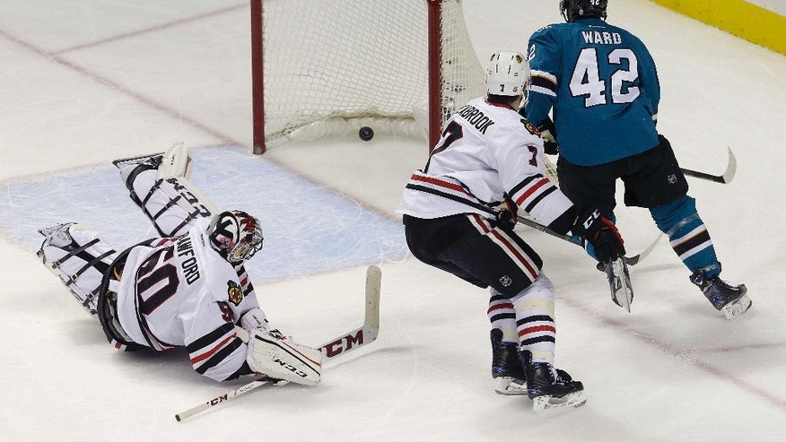 San Jose Sharks right wing Joel Ward (42) scores a goal past Chicago Blackhawks goalie Corey Crawford (50) and defenseman Brent Seabrook (7) during the first period of an NHL hockey game in San Jose, Calif., Wednesday, Nov. 23, 2016. (AP Photo/Jeff Chiu)