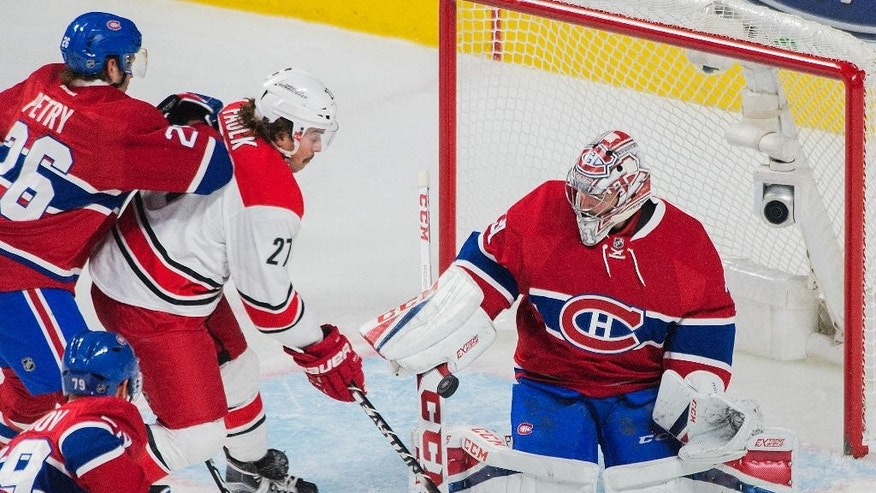 Montreal Canadiens goaltender Carey Price makes a save against Carolina Hurricanes' Justin Faulk (27) as Canadiens' Jeff Petry defends during the first period of an NHL hockey game in Montreal, Thursday, Nov. 24, 2016. (Graham Hughes/The Canadian Press via AP)