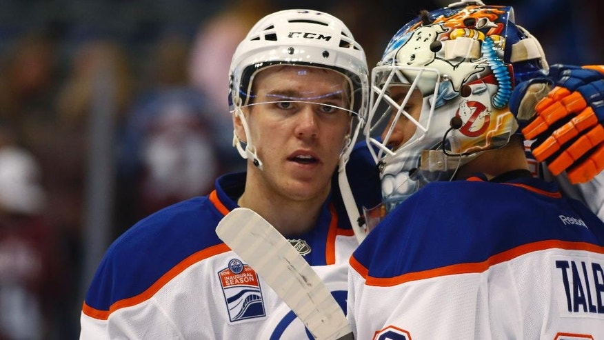 Edmonton Oilers center Connor McDavid, left, congratulates goalie Cam Talbot after the Oilers defeated the Colorado Avalanche in an NHL hockey game Wednesday, Nov. 23, 2016, in Denver. (AP Photo/David Zalubowski)