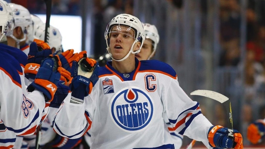 Edmonton Oilers center Connor McDavid is congratulated as he passes the team box after scoring a goal against the Colorado Avalanche during the third period of an NHL hockey game Wednesday, Nov. 23, 2016, in Denver. (AP Photo/David Zalubowski)