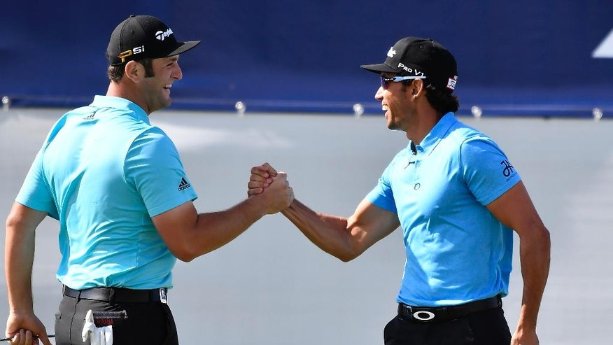 Spain's Rafa Cabrera Bello, right, is congratulated by his partner Jon Rahm after sinking a birdie putt on the 18th green during his match at the World Cup of Golf at Kingston Heath in Melbourne, Australia, Thursday, Nov. 24, 2016. (AP Photo/Andrew Brownbill)