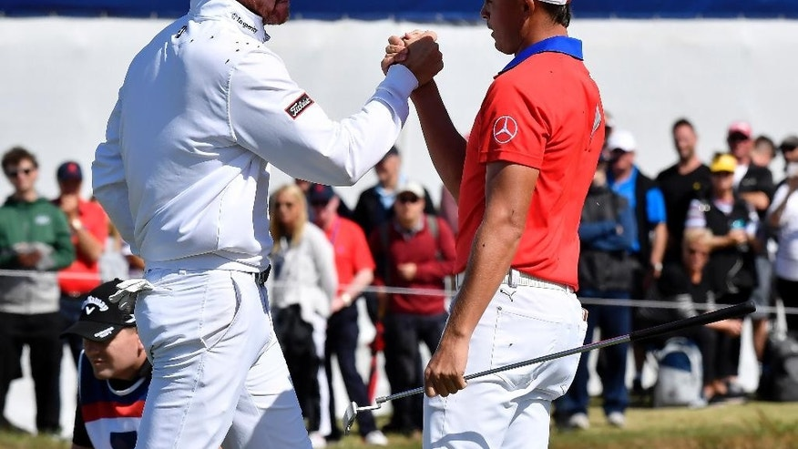 United States' Rickie Fowler, right, shakes hands with teammate Jimmy Walker following their match at the World Cup of Golf at Kingston Heath in Melbourne, Australia, Thursday, Nov. 24, 2016. (AP Photo/Andrew Brownbill)