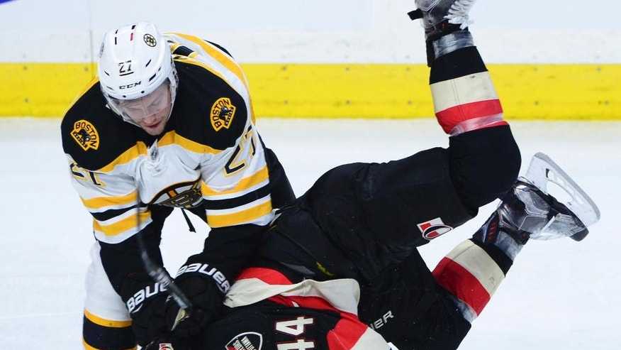 Boston Bruins' Austin Czarnik (27) upends Ottawa Senators' Jean-Gabriel Pageau (44) during third-period NHL hockey game action in Ottawa, Thursday, Nov. 24, 2016. (Sean Kilpatrick/The Canadian Press via AP)