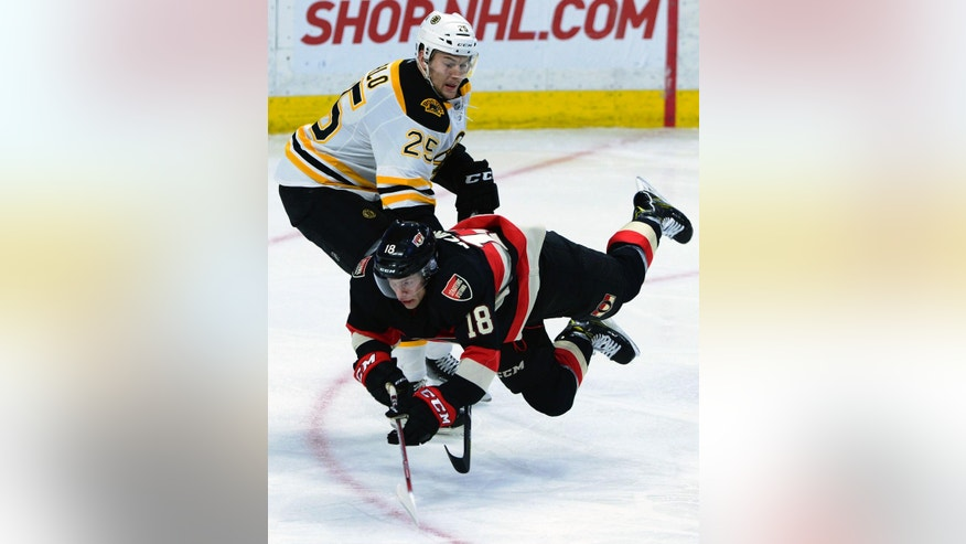 Ottawa Senators' Ryan Dzingel (18) flies in front of Boston Bruins' Brandon Carlo during third-period NHL hockey game action in Ottawa, Thursday, Nov. 24, 2016. (Sean Kilpatrick/The Canadian Press via AP)