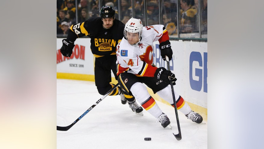 Calgary Flames' Garnet Hathaway (64) handles the puck behind the net ahead of Boston Bruins' Adam McQuaid (54) during the first period of an NHL hockey game in Boston, Friday, Nov. 25, 2016. (AP Photo/Michael Dwyer)