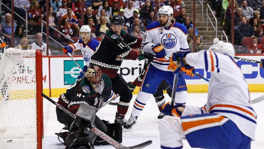 Edmonton Oilers defenseman Adam Larsson, right, scores a goal against Arizona Coyotes goalie Mike Smith (41) as Coyotes center Christian Dvorak (18) and Oilers left wing Patrick Maroon (19) look on during the first period of an NHL hockey game Friday, Nov. 25, 2016, in Glendale, Ariz. (AP Photo/Ross D. Franklin)