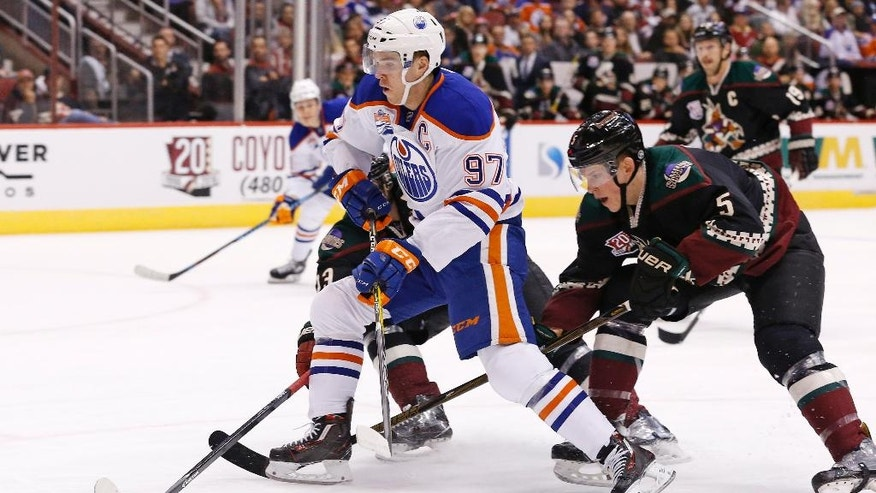 Edmonton Oilers center Connor McDavid (97) tries to skate past Arizona Coyotes defenseman Connor Murphy (5) during the first period of an NHL hockey game Friday, Nov. 25, 2016, in Glendale, Ariz. (AP Photo/Ross D. Franklin)