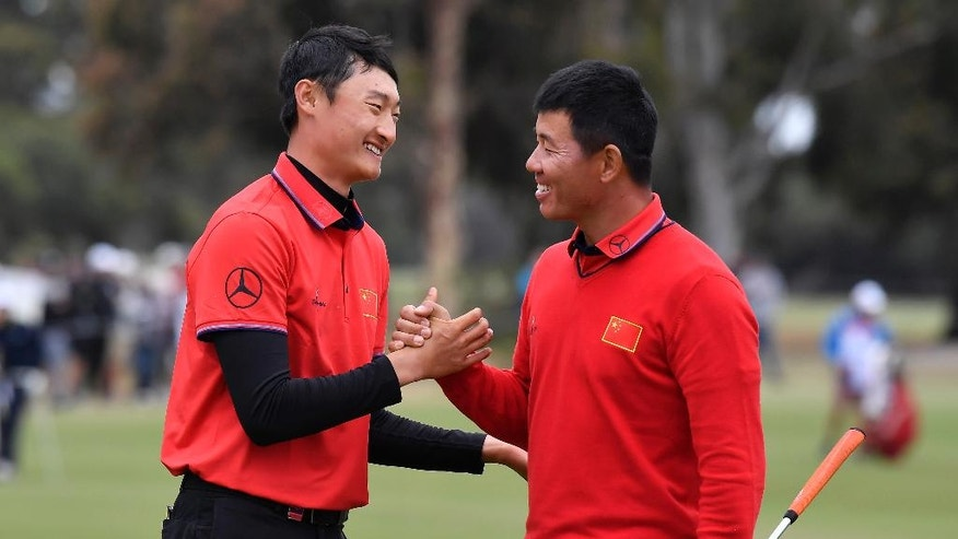 China's Wu Ashun, right, and compatriot China's Li Haotong shake hands on the 18th green following their match at the World Cup of Golf at Kingston Heath in Melbourne, Australia, Friday, Nov. 25, 2016. (AP Photo/Andrew Brownbill)