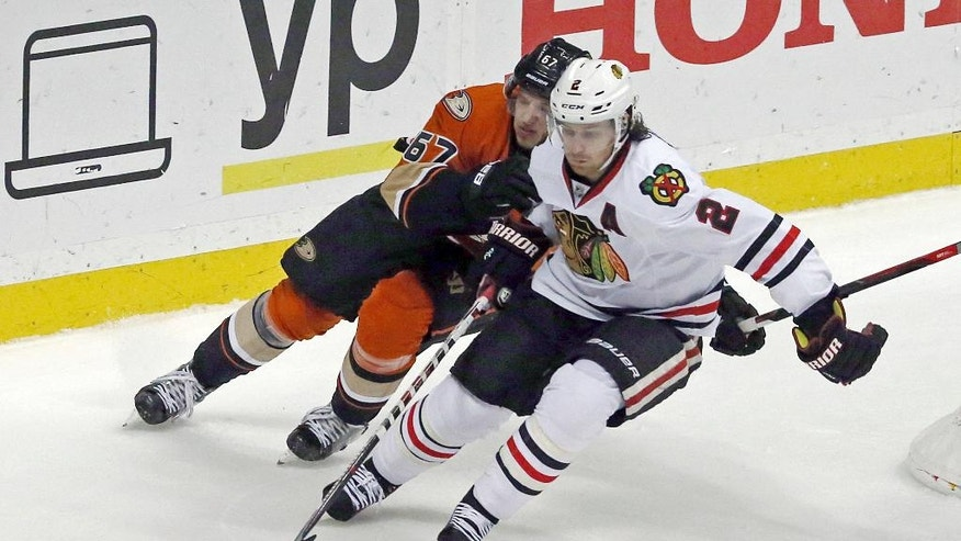 Anaheim Ducks center Rickard Rakell (67) and Chicago Blackhawks defenseman Duncan Keith (2) chase the puck in the second period of an NHL hockey game in Anaheim, Calif., Friday, Nov. 25, 2016. (AP Photo/Reed Saxon)