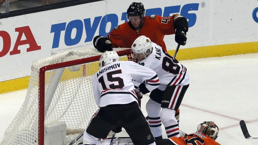 Chicago Blackhawks center Artem Anisimov (15) puts the goal in the net with an assist from right winger Patrick Kane (88) over Anaheim Ducks goalie John Gibson (36) in the first period of an NHL hockey game in Anaheim, Calif., Friday, Nov. 25, 2016. (AP Photo/Reed Saxon)