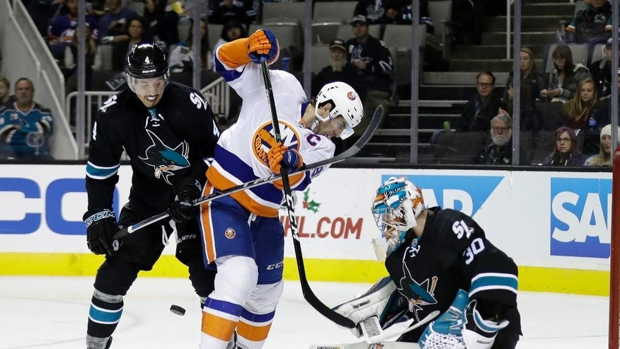 San Jose Sharks goalie Aaron Dell, right, deflects a shot next to New York Islanders' John Tavares, center, and Sharks' Brenden Dillon during the second period of an NHL hockey game Friday, Nov. 25, 2016, in San Jose, Calif. (AP Photo/Marcio Jose Sanchez)