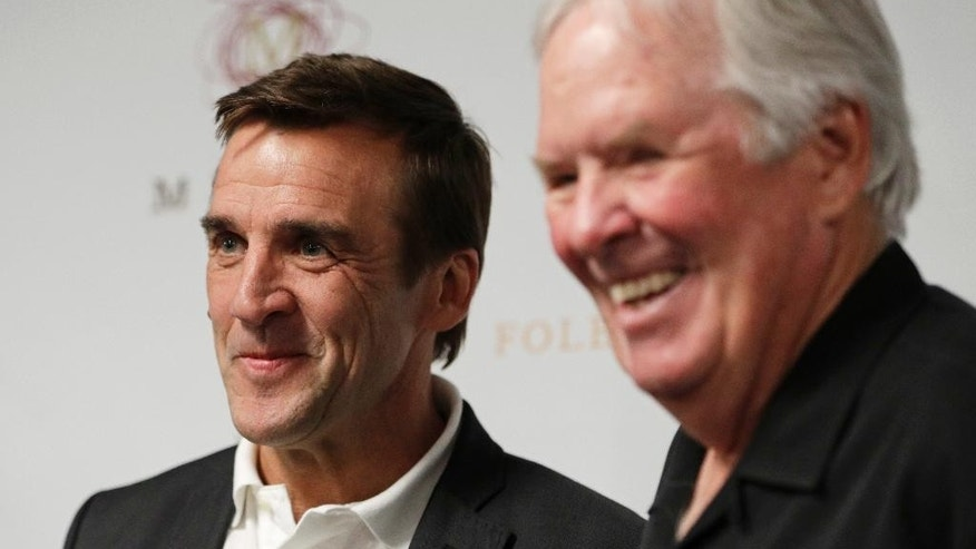 FILE - In this Wednesday, July 13, 2016, file photo, George McPhee, left, and NHL's expansion Las Vegas franchise owner Bill Foley attend a news conference in Las Vegas. Preparations for the Vegas Golden Knights' NHL hockey expansion draft is well underway around the NHL. Vegas general manager McPhee and his colleagues are in the process of putting together mock-ups and getting ready for June, the league's first expansion draft since 2000. (AP Photo/John Locher, File)