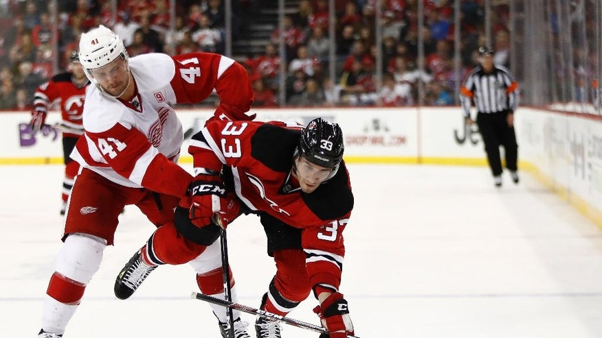 Detroit Red Wings center Luke Glendening (41) and New Jersey Devils defenseman Yohann Auvitu (33), of France, compete for the puck during the second period of an NHL hockey game, Friday, Nov. 25, 2016, in Newark, N.J. (AP Photo/Julio Cortez)