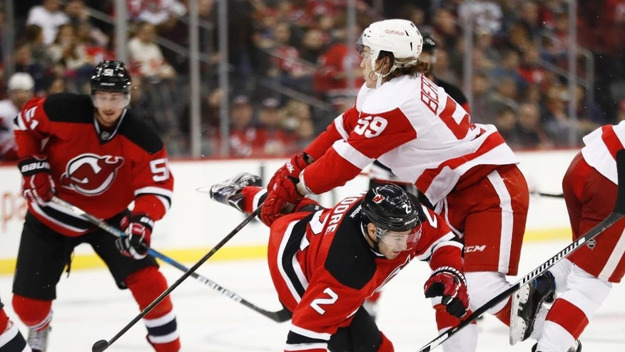 New Jersey Devils defenseman John Moore (2) is knocked down by Detroit Red Wings left wing Tyler Bertuzzi (59) during the second period of an NHL hockey game, Friday, Nov. 25, 2016, in Newark, N.J. (AP Photo/Julio Cortez)