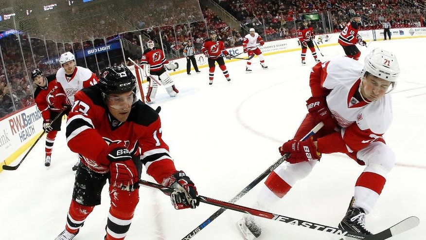 New Jersey Devils left wing Michael Cammalleri (13) and Detroit Red Wings center Dylan Larkin (71) compete for the puck during the first period of an NHL hockey game, Friday, Nov. 25, 2016, in Newark, N.J. (AP Photo/Julio Cortez)