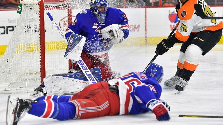 New York Rangers goalie Henrik Lundqvist, center, makes a save past Philadelphia Flyers' Pierre-Edouard Bellemare, right, as defenseman Brady Skjei falls to the ice during the second period of an NHL hockey game, Friday, Nov. 25, 2016, in Philadelphia. (AP Photo/Derik Hamilton)