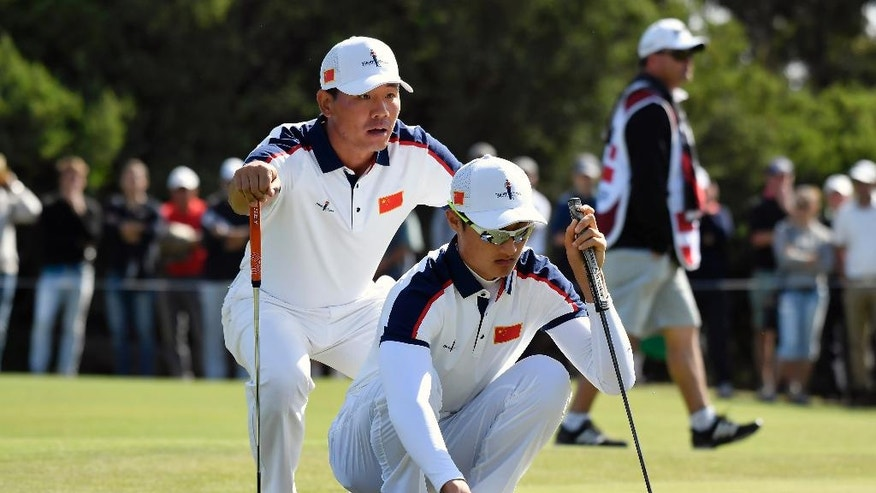 China's Wu Ashun, left, and compatriot Li Haotong line up a putt on the17th green during their match at the World Cup of golf at Kingston Heath in Melbourne, Australia, Saturday, Nov. 26, 2016. (AP Photo/Andrew Brownbill)