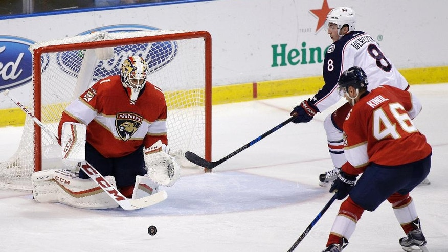 Florida Panthers goalie Roberto Luongo (1) and defenseman Jakub Kindl go for the puck against Columbus Blue Jackets defenseman Zach Werenski (8) during the second period of an NHL hockey game, Saturday, Nov. 26, 2016, in Sunrise, Fla. (AP Photo/Terry Renna)
